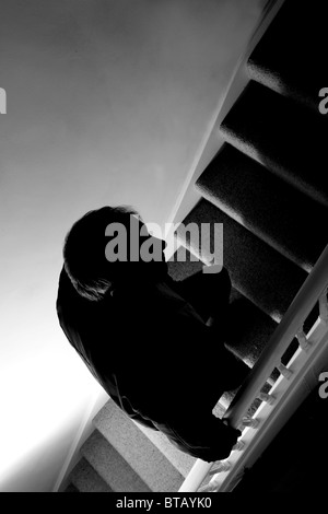Silhouette of a man walking up a dark stairway - Stock Photo