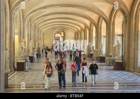 Group of tourists visitors entering Louvre Museum Paris - Stock Photo