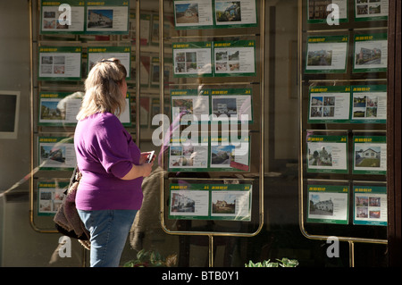 A single woman looking at property details house for sale in the window of an estate agents UK - Stock Photo