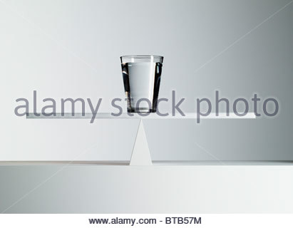 Glass of water balancing on middle of seesaw - Stock Photo