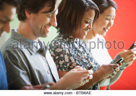 Smiling men and women text messaging on cell phones in a row - Stock Photo