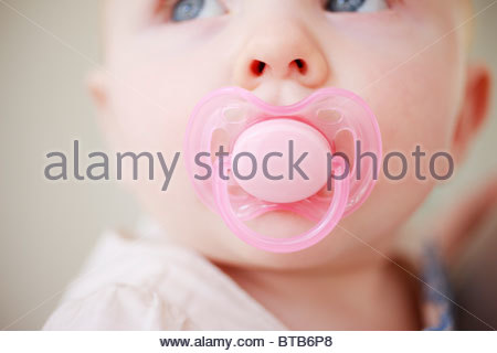 Close up of baby with pink pacifier - Stock Photo
