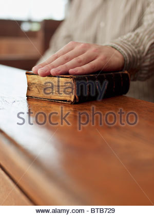 Hand of witness on Bible in courtroom - Stock Photo