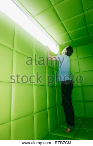 Man reaching to look out window in padded room - Stock Photo