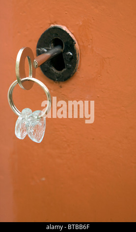 Old fashioned key in door lock - Stock Photo