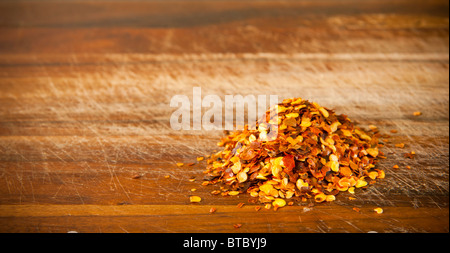 Pile of red chilli seeds on a timber board - Stock Photo