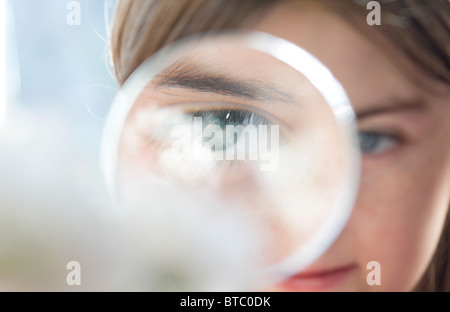 young female girl looking through magnifying glass - Stock Photo