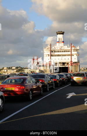 Queuing cars wait in line to board a cross channel ferry at St Malo western France - Stock Photo