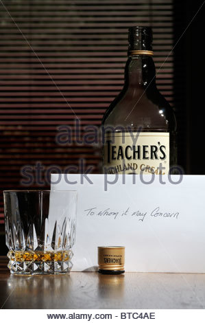 Close up image of a To Whom It May Concern suicide note left on kitchen table alongside a bottle and tumbler of - Stock Photo