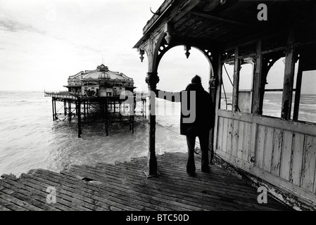 A person standing at the shore end of the desolate West Pier in Brighton - Stock Photo
