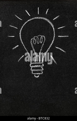 Light bulb drawn on a blackboard with copy space - Stock Photo