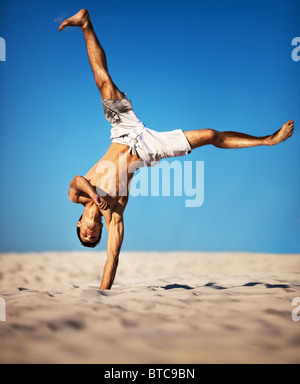 Young sportsman on beach. On blue sky background. - Stock Photo