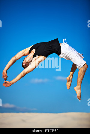 Young man jumping on beach. - Stock Photo