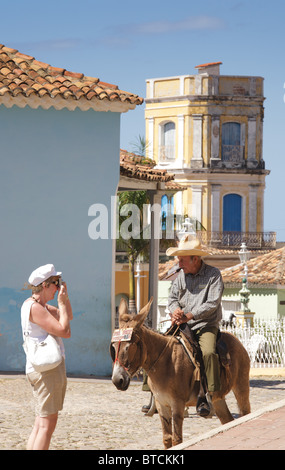 TRINIDAD: CUBAN MAN ON DONKEY AND TOURISTS - Stock Photo