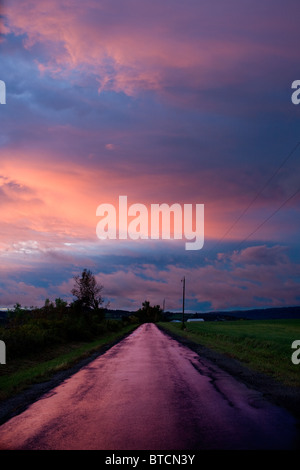 Road runs into sunset, farm country, Mohawk Valley, Herkimer County, New York State - Stock Photo