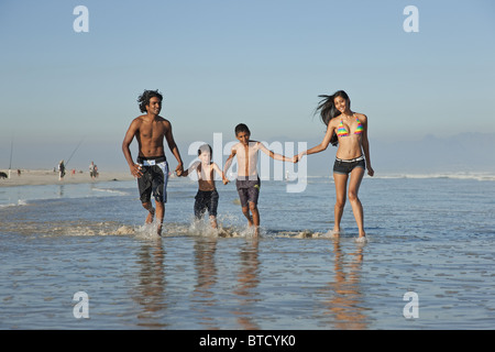 Indian family, dressed in swim wear, playing in shallow waves. - Stock Photo