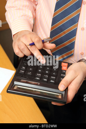 businessman counts money on calculator - close-up view - Stock Photo