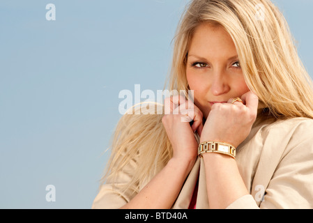 blonde woman at the beach keeping warm with collar jacket up - Stock Photo