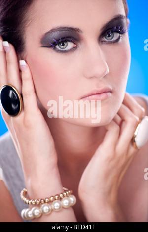 woman with smokey eye make up wearing rings and bracelets, fashion jewellery - Stock Photo