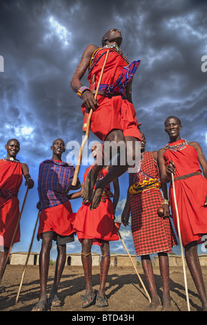 Masai warriors doing the traditional  jump dance circle is formed and one or two warriors will enter the circle - Stock Photo
