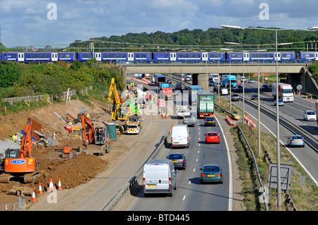 Road widening works on M25 motorway with train on bridge - Stock Photo
