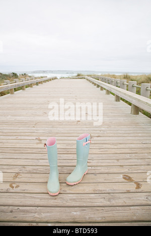 Pair of rubber boots at the coast - Stock Photo
