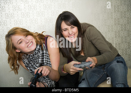 Teenage girls playing on games console - Stock Photo