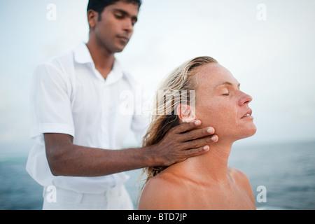 Woman having her neck massaged, South Huvadhu Atoll, Maldives - Stock Photo