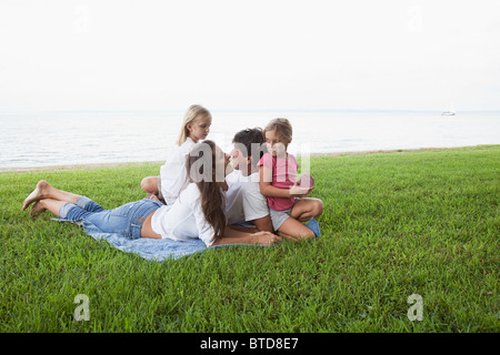 Family relaxing on grass by the sea - Stock Photo
