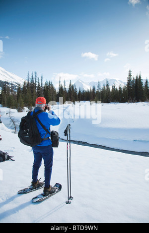 Man on snowshoes views the scenery at Glacier Creek near Johnson Pass Trail, Chugach National Forest, Kenai Peninsula, - Stock Photo