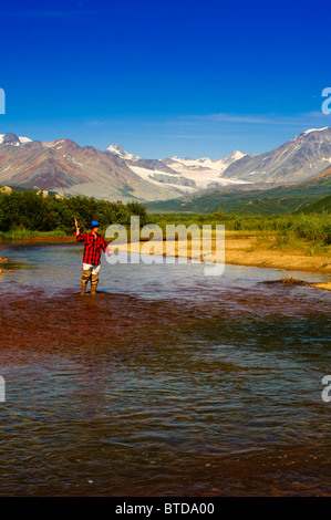 Man fly fishing in Gunn Creek off the Richardson Highway with Gulkana Glacier and the Alaska Range in the background, - Stock Photo