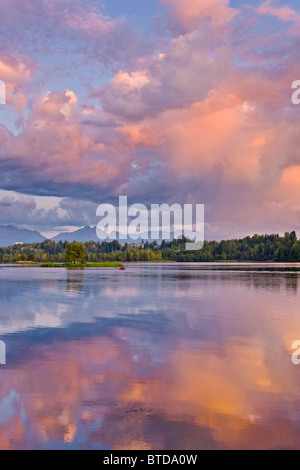 Couple kayaking in Westchester Lagoon at with pink clouds reflecting in the water at sunset, Downtown Anchorage, - Stock Photo
