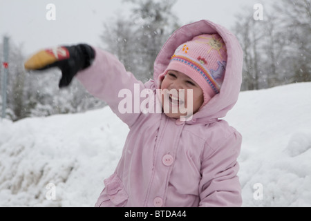 A young girl playing in the snow throwing snowballs and laughing dressed in pink - Stock Photo