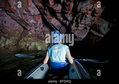 A young woman exploring a marine cave of the Crozon peninsula (Brittany). Jeune femme explorant une grotte marine - Stock Photo