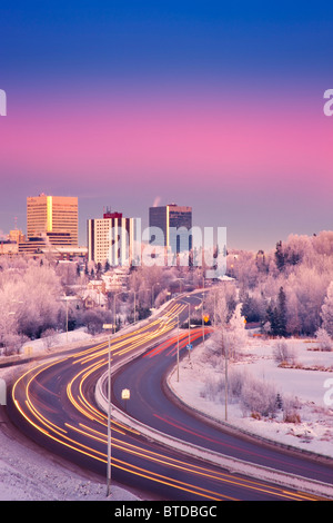 Sunset view of traffic on Minnesota Blvd. with downtown Anchorage in the background, Southcentral Alaska, Winter/n - Stock Photo
