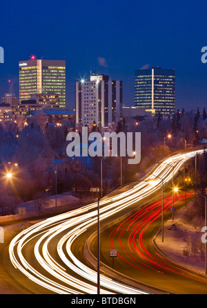 Twilight view of traffic on Minnesota Blvd. with downtown Anchorage in the background, Southcentral Alaska, Winter/n - Stock Photo