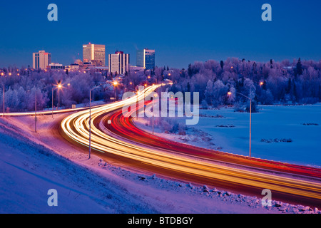 Twilight view of traffic on Minnesota Blvd. with downtown Anchorage in the background, Southcentral Alaska, Winter - Stock Photo