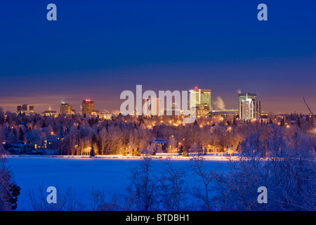 Skyline view of downtown Anchorage and Westchester Lagoon at twilight, Southcentral Alaska, Winter - Stock Photo