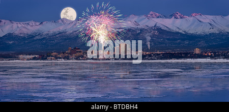 Panoramic of moon rising over the Anchorage skyline and Chugach Mountains at dusk with  fireworks overhead, Alaska, - Stock Photo
