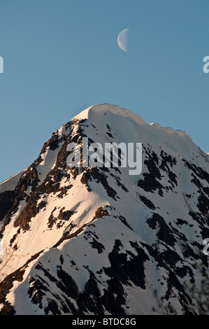 A half-moon passes over a snow-crested peak in Portage Valley, Chugach National Forest, Southcentral Alaska, Spring - Stock Photo