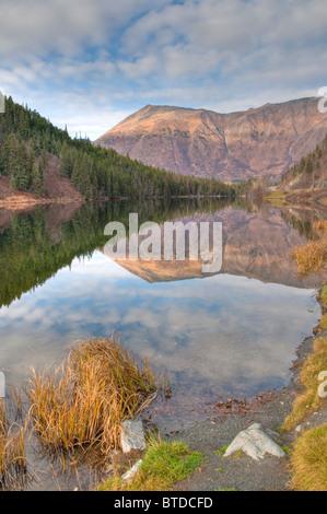 View of mountains reflected in Jerome Lake near the juction of Seward and Sterling Highways, Kenai Peninsula, Alaska - Stock Photo