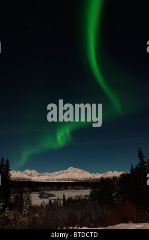 View of green Northern Lights (Aurora borealis) arching through the night sky over Denali State Park, Interior Alaska, - Stock Photo