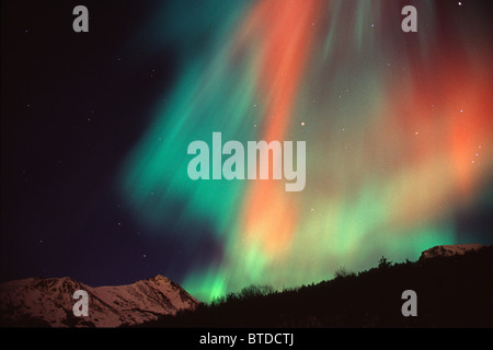 Multi colored Northern Lghts fill the night sky and cast colored shadows on the mountain tops of Chugach State Park, - Stock Photo