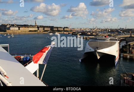 French national flag flying from the stern of a ship with the backdrop of St Malo a historic town and port in western - Stock Photo