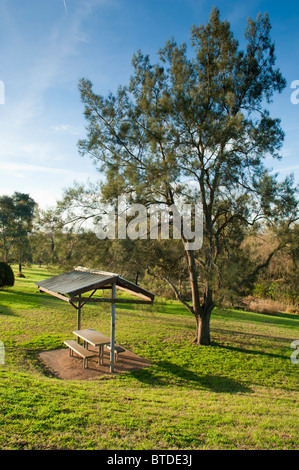 Small shelter in green parkland with seats and a table - Stock Photo