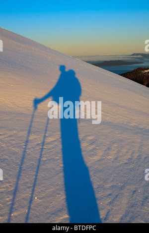 A skier casts a long shadow over the snow at dawn as he ascends a mountain on Wrangell Island, Alaska - Stock Photo