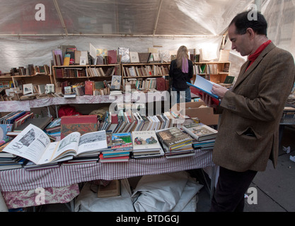 Bookstall at outdoor weekend antiques market on streets of Paris France - Stock Photo
