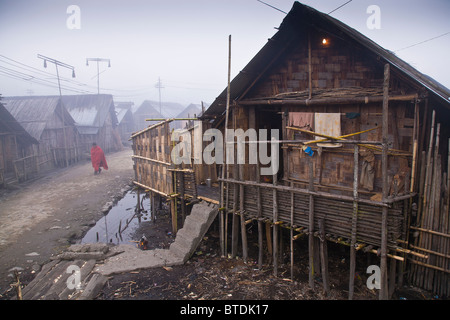 An Apatani tribal man walks through the rows of bamboo huts on stilts in the village of Hijja, Arunachal Pradesh. - Stock Photo