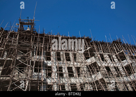 Construction and wooden scaffolding and screens in downtown Awassa on a multi-story building - Stock Photo