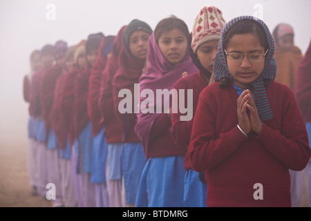 A group of school children in a rural village assemble to pray and do exercises before school lessons begin, Chita - Stock Photo